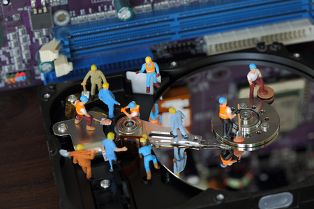 fixed disk: Selective focus of miniature engineer and worker maintenance hard disk and fixed problem hard disk of Personal computer (PC) on mainboard background as business and industrial concept. Stock Photo
