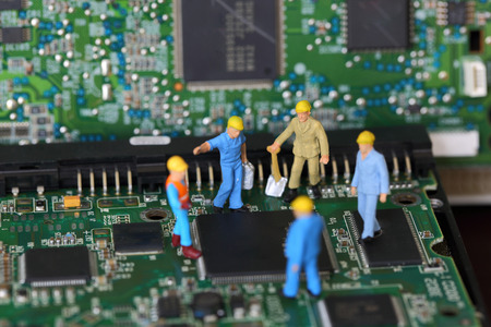 mainboard: Selective focus of miniature engineer discuss and worker fixed problem on chips and mainboard as business and industrial concept.