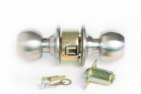 Close up of stainless steel round ball door knob on white background as Locksmith and industrial concept. Stock Photo