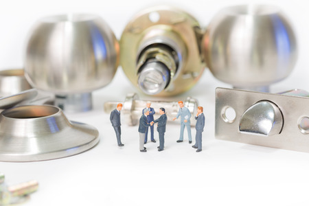 Selective focus of miniature businessman handshake and stainless steel round ball door knob components as commitment, business and locksmith concept. Stock Photo