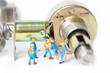 Selective focus of miniature engineer and worker prepare Stainless steel round ball door knob component on white background as Locksmith, business and industrial concept. Stock Photo