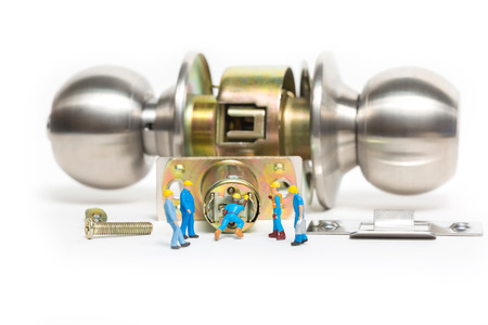 Selective focus of miniature engineer and worker build Stainless steel round ball door knob components on white background as Locksmith, business and industrial concept. Stock Photo
