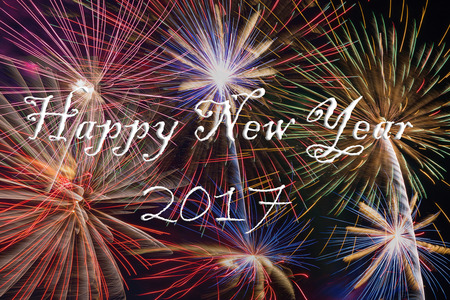 white work: Happy New Year 2017 text on Colorful fireworks of various colors over sky at night - use for celebration background and texture.
