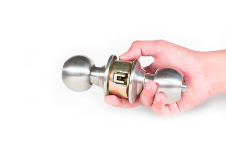 Hand hold stainless steel round ball door knob isolated on white background as Locksmith and industrial concept. Stock Photo