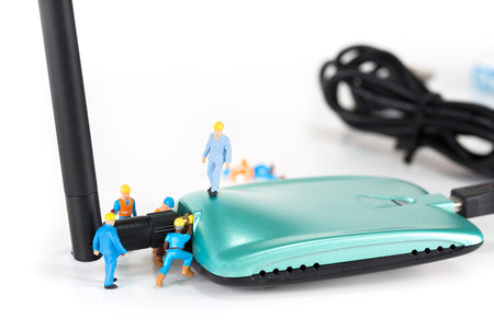 Selective focus of miniature engineer and worker install antenna to wireless router as technology, communication and network concept.
