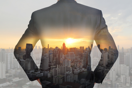 A back turned businessman cityscape and sunset as vision of leader concept. Stock Photo