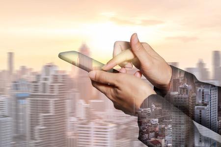 banco mundial: Doble exposición de mujer mano pantalla táctil teléfono inteligente, paisaje urbano móvil y puesta del sol como concepto de tecnología y telecomunicaciones. Uso para producto o presentación de fondo de tecnología.