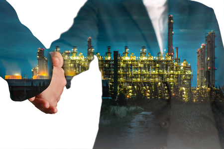 Double exposure of handshake and gas and oil refinery industry plant at twilight isolated on white background as commitment of energy concept.