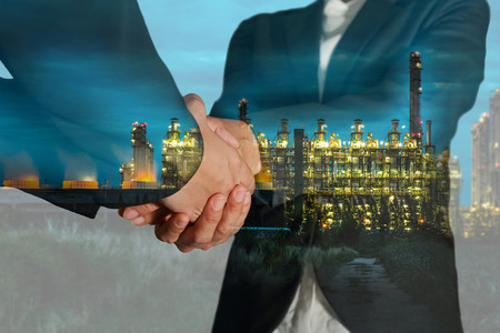 Double exposure of business women double handshake and gas refinery industry plant, Electric Generating Factory at twilight as Partnership of Energy concept.