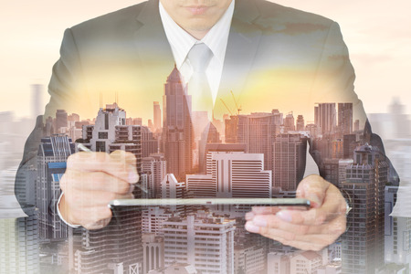 Double exposure of business man working with tablet, cityscape and sunset as telecommunication and technology concept.