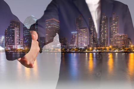 Double exposure of handshake, city, urban and lake at night as Teamwork concept.