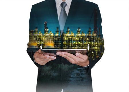 Double exposure of business man hand hold tablet and gas refinery industry plant at twilight isolated white background as Research of Energy concept.