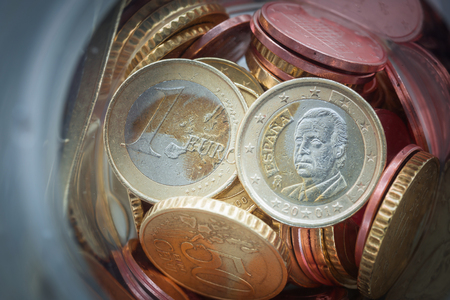 Closeup of Euro coins in bottle and shadow as business, money, banking, currency and exchange rate concept