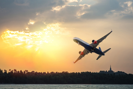 Airplane flying through the sea at sunset Stock Photo