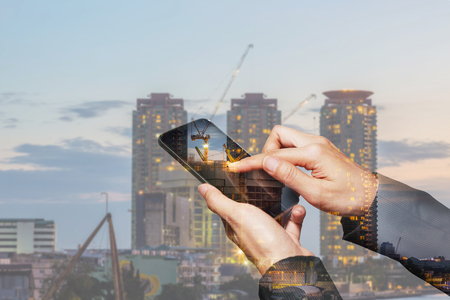 Double exposure of woman hand hold and touch screen smartphone, cellphone, construction crane and building in the evening, twilight as business, construction and high speed of communication concept.