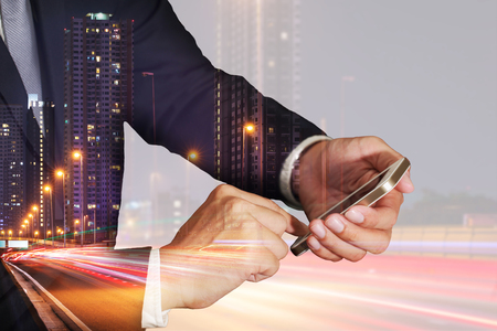 Double exposure of businessman use smartphone, light trails on the street and urban in the night as business, Technology, telecommunication and Communication concept. Stock Photo