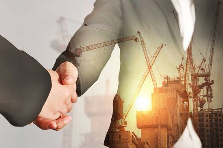 Double exposure of handshake, construction crane, building and sunset in the evening as business, relationship, partnership, commitment and industry concept. Stock Photo