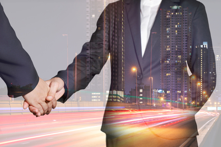 Double exposure of businesswomen handshake, light trails on the street and urban in the night as business, commitment, partnership and congratulation concept. Stock Photo