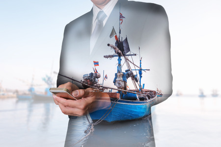 Double exposure of businessman hand hold smartphone, mobile, fishing boat and sea as business, technology, communication and industry concept.