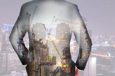 사업가의 이중 노출 다시, 건설 크레인, 건물, 도시 및 황혼 또는 저녁 산업, 비즈니스 및 리더 개념의 비전으로 도시를 찾고.