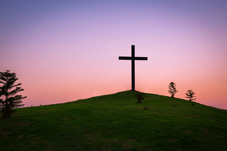The cross is buried on a grassy hill and meadow in the twilight, abstract nature background as Christianity concept. Stock Photo