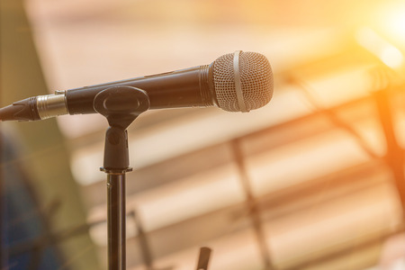 Microphone on abstract blurred indoor background with sunlight of sunset