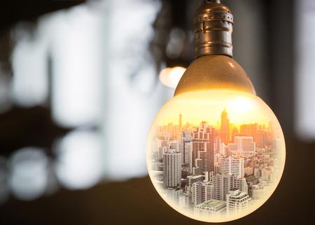 ビジネスやグローバル化と思うアイデアの概念として大きな円の電球で夕暮れ時の街並み。
