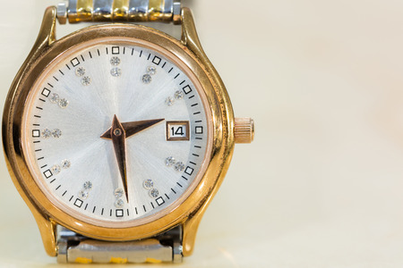 Close-up front view of Luxury golden hand watch. Best accessories background. Stock Photo