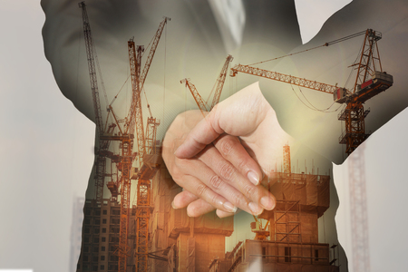 Double exposure of handshake, construction crane, building and sunset in the evening as business, commitment and industry concept.