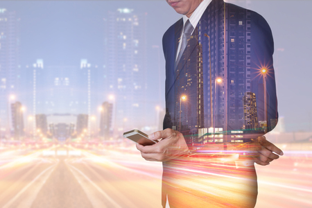 Double exposure of businessman stand up and research by smartphone, light trails on the street and urban at dusk, night as technology, communication and business concept. Stock Photo