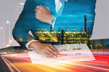 Businessman hand put on the chart document, light trails on the street and urban, Electric generating factory industry in the night as energy, business, meeting and analysis concept. Stock Photo