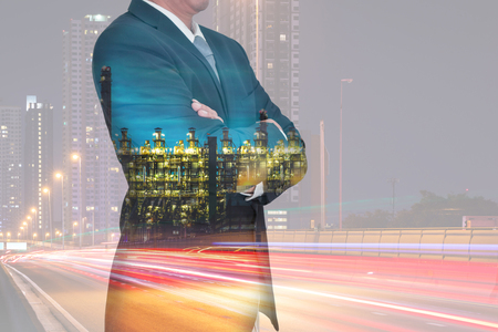 Double exposure of Businessman arms crossed and stand up, light trails on the street and urban, Electric generating factory industry in the night as business and construction concept.