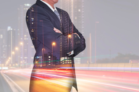 Double exposure of Businessman arms crossed and stand up and light trails on the street and urban in the night as thinking vision of leader concept.