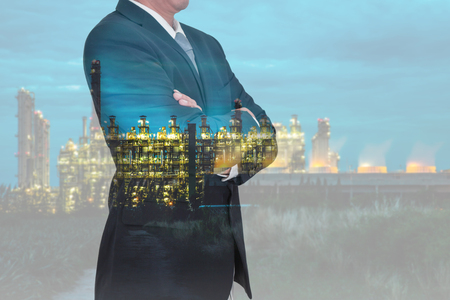 Double exposure of Businessman arms crossed and stand up and Electric generating factory industry in the night as business, thinking vision of leader and energy concept.