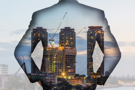 A back turned businessman and construction crane and building in the evening, twilight as business, vision of leader and industrial concept