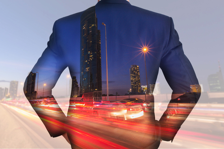 A back turned businessman, light trails on the street and urban at dusk, night as business and vision of leader concept Stock Photo