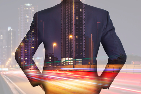 A back turned businessman, light trails on the street and urban in the night as business and vision of leader concept 版權商用圖片
