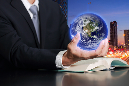 Businessman hand hold the Earth on light trails street city in the night as business, control and Saving World concept.