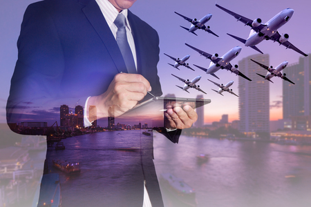 Double exposure of businessman working with tablet, airplane flying, city,urban and river in the night as business, transportation, travel, technology and communication concept. Reklamní fotografie