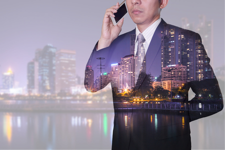 Double exposure of businessman calling with smartphone, lake and urban in the night as business, technology, communication and telecommunication concept.