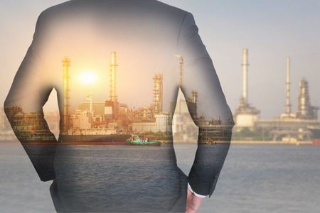 Double exposure of businessman Back, looking ahead, oil fuel, Electric generating factory near the river and sunset as business, vision of leader, industry and energy concept. Standard-Bild