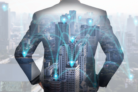 Double exposure of A back turned businessman, city and urban in the foggy morning with pin node networking as busines. Stock Photo