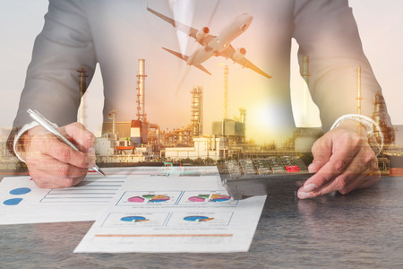 Double exposure of businessman working with document and calculator for analyze in the work, airplane, fuel, Electric generating factory or plant with sunset as business, industry and energy concept. Banco de Imagens