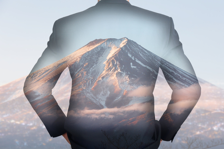 Double exposure of A back turned businessman and Fuji mountain with sunlight in the morning as business, vision of leader and travel concept.
