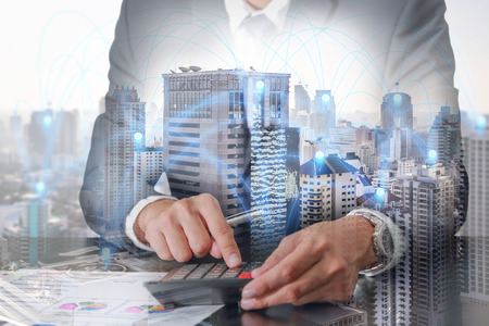 Double exposure of businessman working with calculator, cityscape and urban with node of networking as business, worker, technology, communication and Calculation concept