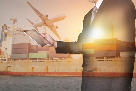 Double exposure of businessman looking the tablet, container cargo ship, cargo plane and airplane at sunset as business, technology, industrial, transportation, logistic and import export concept Stock Photo