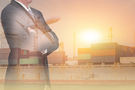 Double exposure of Businessman arms crossed, container cargo ship, cargo plane and airplane at sunset as business, industrial, transportation, logistic and import export concept.