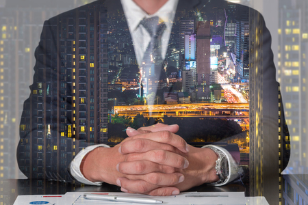 Double exposure of businessman fingers crossed and sit down, cityscape, urban and street in the night as meeting, commitment and business concept. Standard-Bild