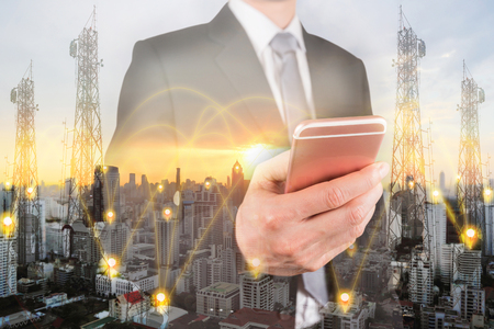 Double exposure of businessman use smartphone, communication node tower or 4G 5G network telephone cellsite and cityscape urban at sunset as business, technology and telecom concept Imagens