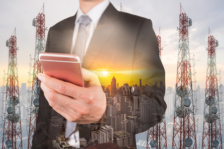 Double exposure of businessman use smartphone, communication node tower or 4G 5G network telephone cellsite and cityscape urban at sunset as business, technology and telecom concept Banque d'images